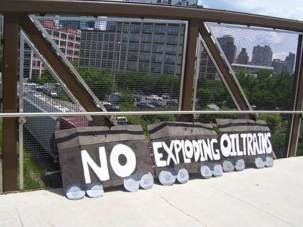 """No Exploding Oil Trains"" banner displayed as shale oil train passes by the morning of  Philadelphia oil trains action, July 9 2014. Photo: Ann Dixon"